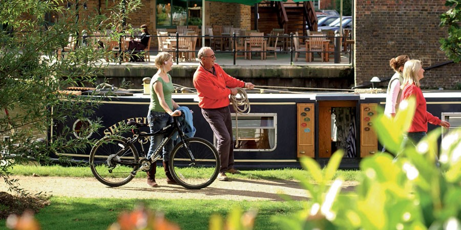 walkers, a cyclist, angler and boater on the Grand Union Canal