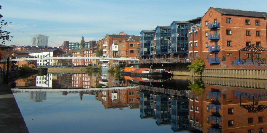 View down River Aire towards Leeds City Centre with moored boats, white bridge and city buildings in background