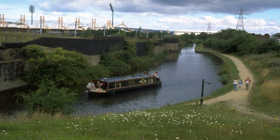 Boat on navigation in front of sports arena, with family walking on towpath
