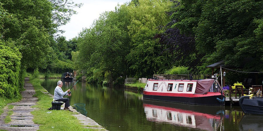 Angler on Macclesfield Canal with boat moored opposite
