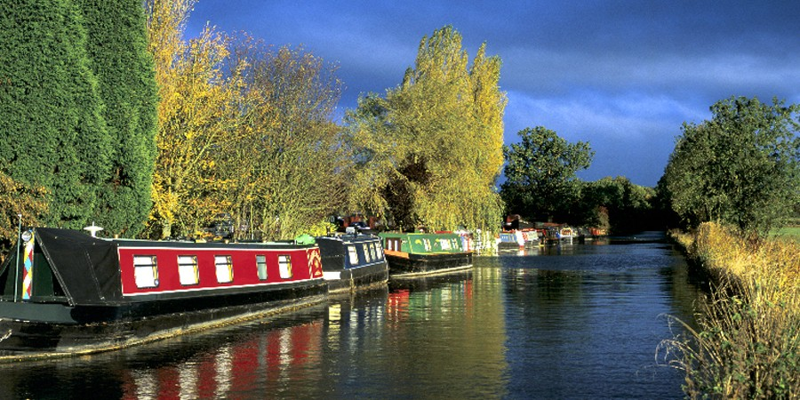 Boats moored along towpath of canal