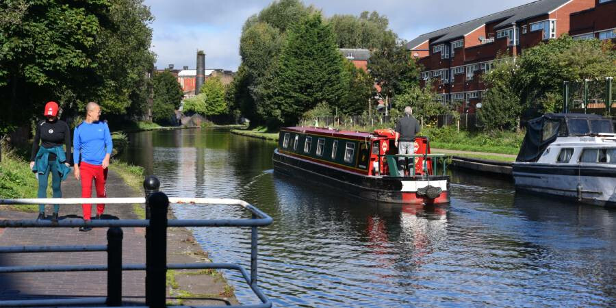 A canal with walkers on the towpath and a boat on the water