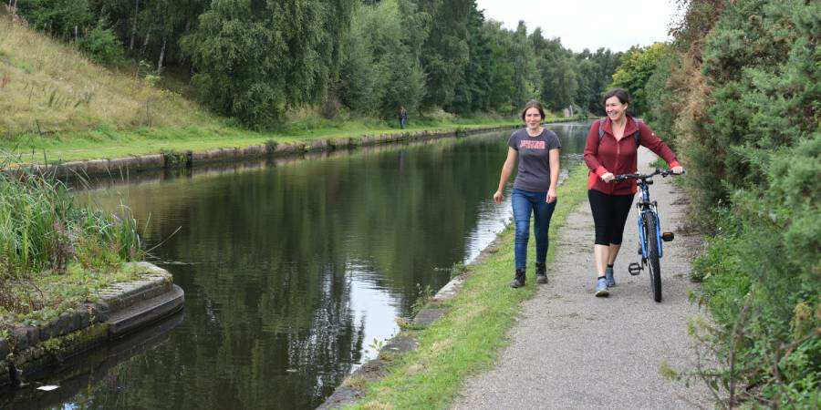 A walker and a dismounted cyclist walking beside a canal in Birmingham