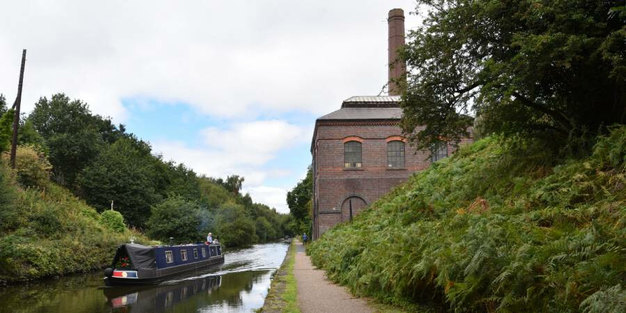 A towpath walking route past a historic building