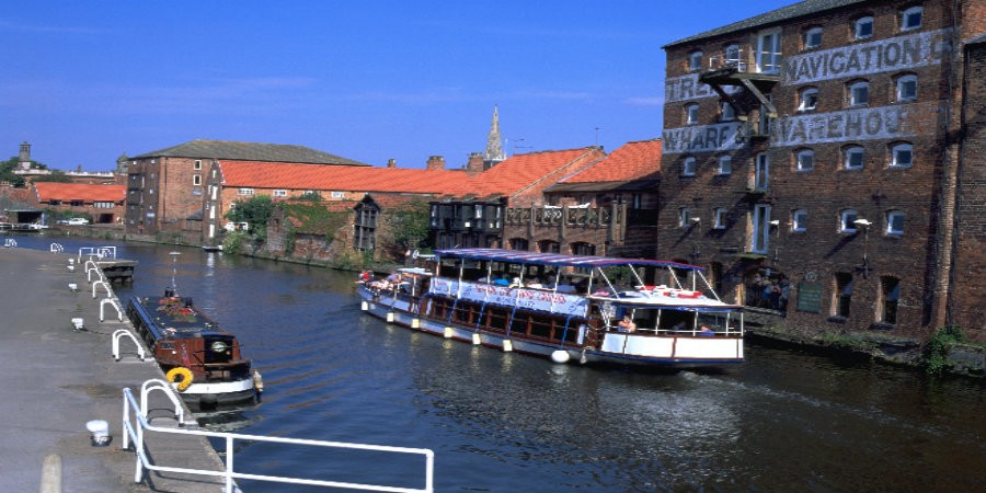 Large trip boat on River Trent in front of wharf warehouse