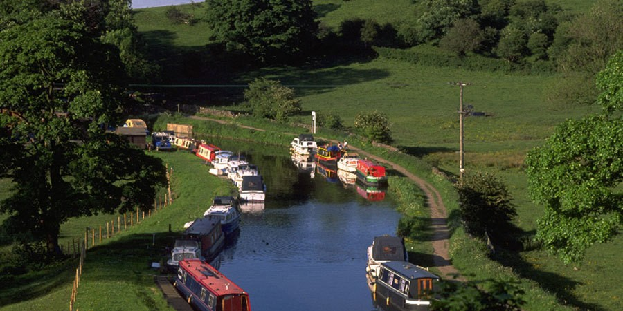 Boats moored along towpath in rural area