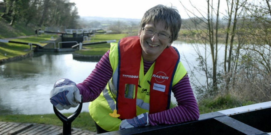 Gill Anlezark, volunteer lock keeper, leaning on lock beam holding spade