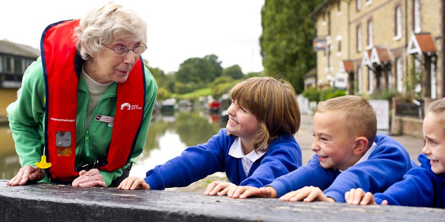 Explorer education volunteer, Olive, in lifejacket with pupils leaning on lock beam