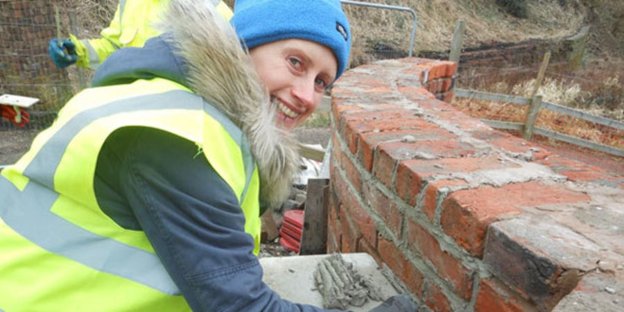 Natalie repointing a wall with lime mortar