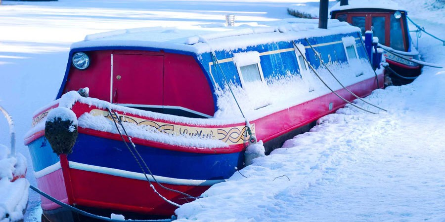 A boat moored in the snow on the Leeds & Liverpool Canal