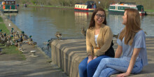 Two girls sitting by the canal