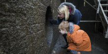 Mother and child looking through hole