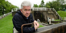 Poet Ian McMillan standing at a canal lock