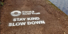 Stay kind slow down message on towpath