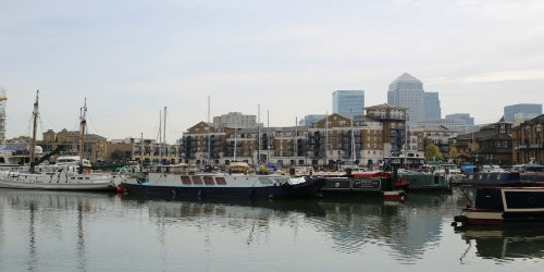 View of Limehouse Basin on Limehouse Cut with boats and flats in the foreground and skyscrapers in the background