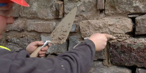 An engineer repointing a wall