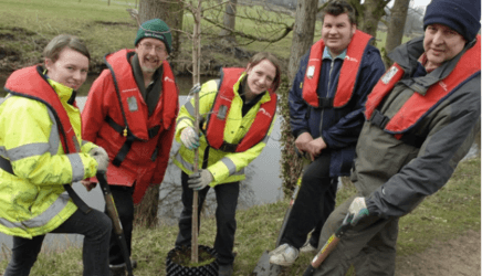 Volunteers planting trees by the canal