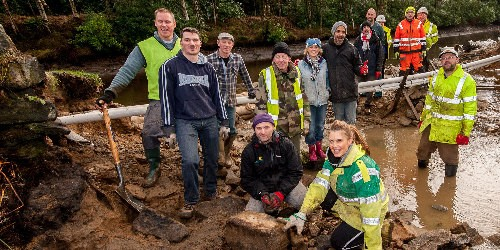 Volunteers by a flood-damaged canal