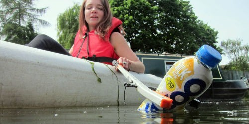 Girl picks litter out of the water from a kayak