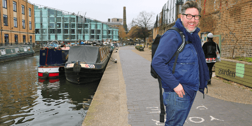Man smiling and walking down the canal