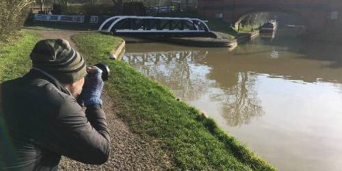 A photographer by a canal