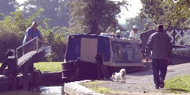 Boat leaving lock with man walking dog on towpath