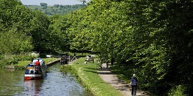 Boat entering lock on Peak Forest Canal with walkers on the towpath