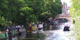 Boats moored along towpath on River Soar, with walkers passing by
