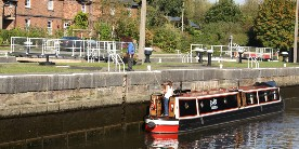 Lady on moored narrowboat talking to volunteer on bank