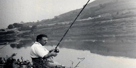Black and white photo of Billy Lane sat angling