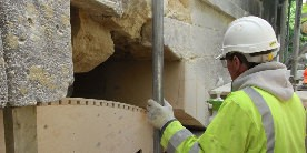 Employee in hi-vis and white hard-hat repairing stonework on bridge