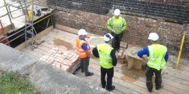 Employees in hi-vis and white hard hats stood on platform in de-watered lock on Grantham Canal