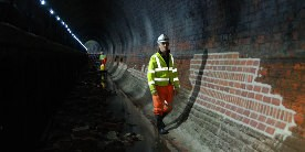 Employee in hi-vis and white hard-hat stood in dewatered tunnel