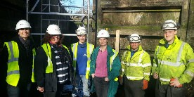 Group of people in hi-vis and white hard-hats stood in dewatered lock