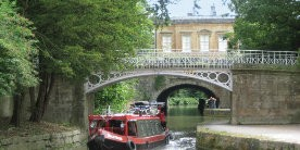 Narrowboat passing under bridge in front of Cleveland House in Bath