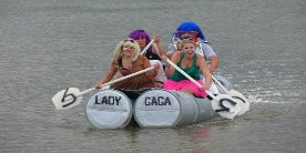 Four people on oil drum raft in fancy dress