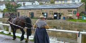 Lady with boat horse stood on opposite bank to Five Rise Cafe