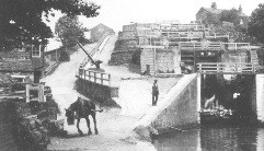 Black and white photo from around 1900: Hauling the boat out of the Five Rise Locks, whilst also having a feed from his nose tin