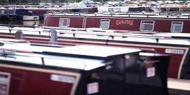 Red narrowboats moored in marina