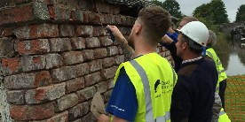 Volunteers repointing brickwork