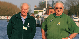 Two men standing by the canal