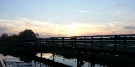 Sunset over the River section, silhouetting the footbridge