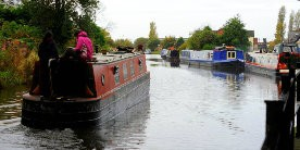 Image of narrowboat cruising past other boats on the canal