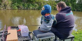 Simon Mottram teaching a child to fish at one of our Let's Fish! events