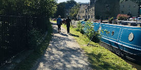 two people walking along towpath in Hebden Bridge beside narrowboat