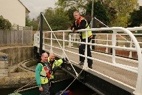 A work boat crew fixing signage (Photo by Mike Gallagher, Cotswold Canals Trust)