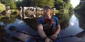 Andy Torbet in canoe with cows