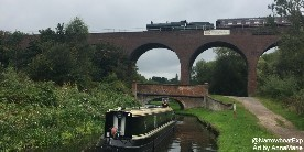 A narrowboat on the Staffs & Worcester canal with a steam train passing behind on the viaduct