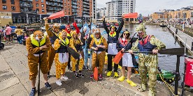 Group of young people in fancy dress by a river, taking part in a fundraising event