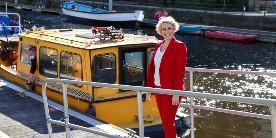 Woman in red dress posing in front of boat